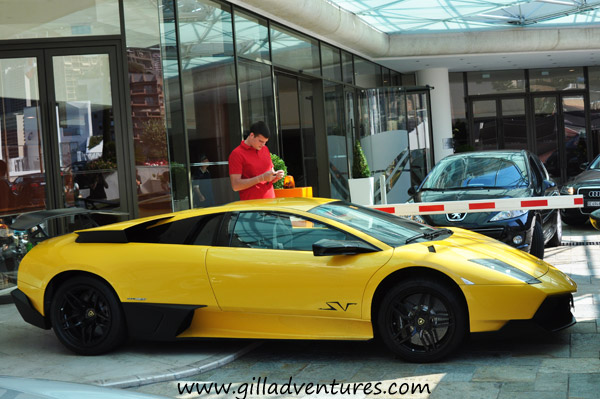 A Lamborghini parked in Monte Carlo, with a passerby taking photos.