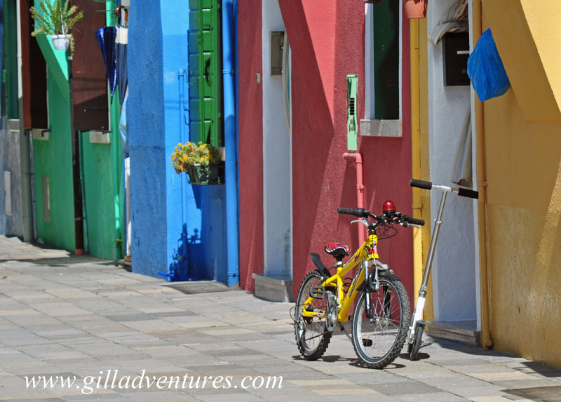 A child&#039;s yellow bike in front of a colorful house on the island of Burano, Italy. 