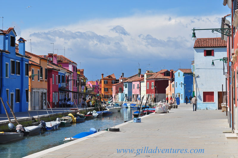 Burano, Italy with colorful buildings, boats in the canal, and storm clouds in the distance.