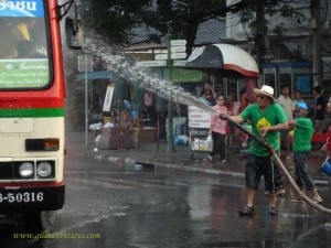 Spraying water from a fire hose on the streets of Bangkok during Songkran Festival.