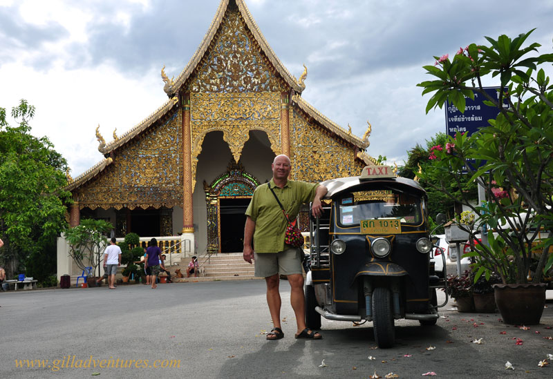 A wat in Chiang Mai with a tuk tuk out front.