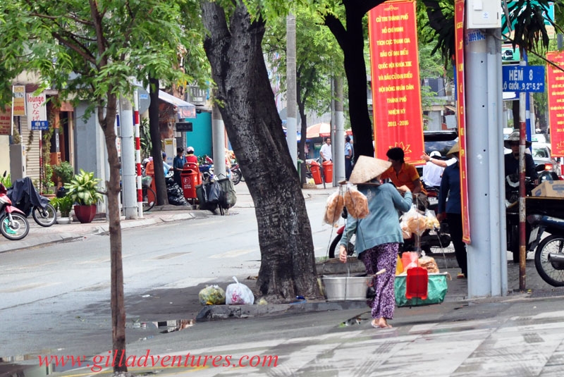 A woman carrying food on the street in Ho Chi Minh City, Vietnam.