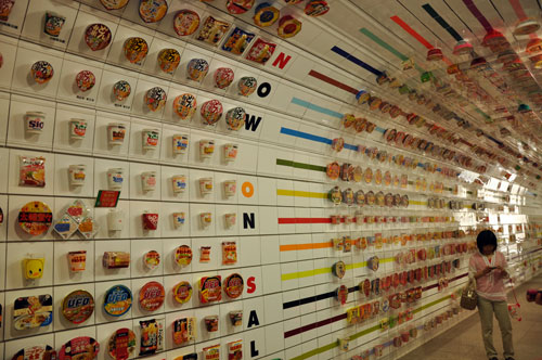 The instant ramen museum timeline tunnel showing the development of flavors and packaging of instant ramen. Photo taken on our RTW trip with teen and tween children. Posted to our travelogue.